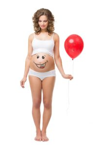 Beautiful girl holding air balloon and looking at her pregnant belly with smily funny face drawn on it. Isolated.